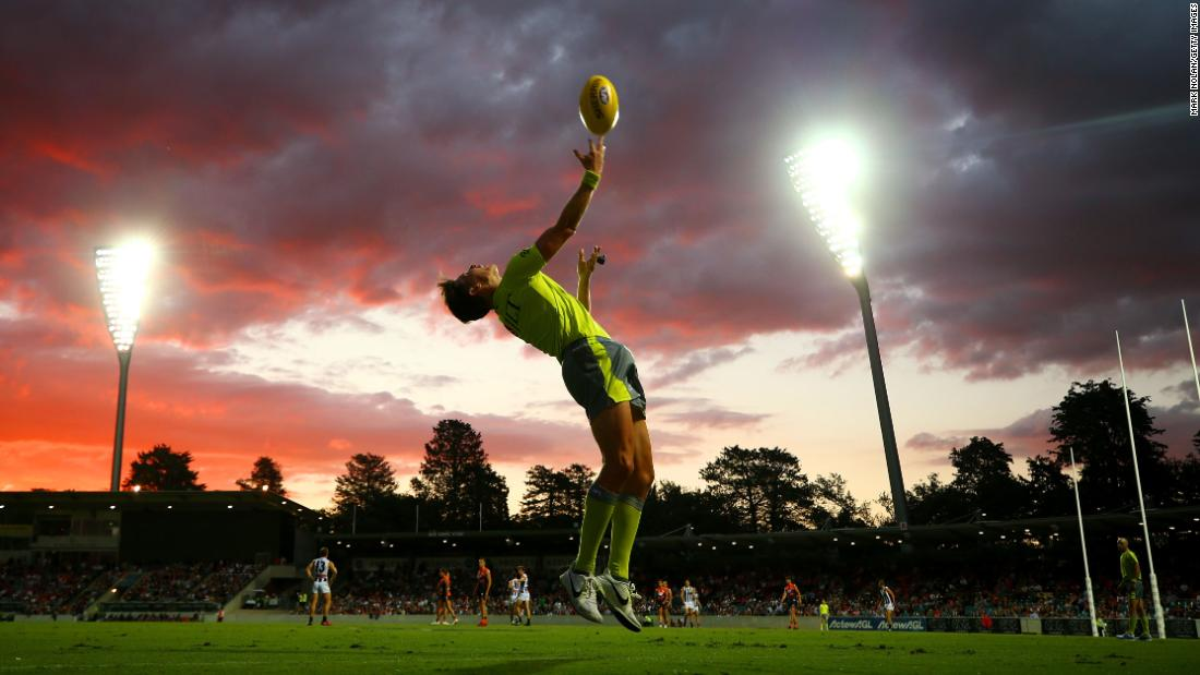 An Australian Football League umpire throws the ball in during a match in Canberra on Thursday, March 1.