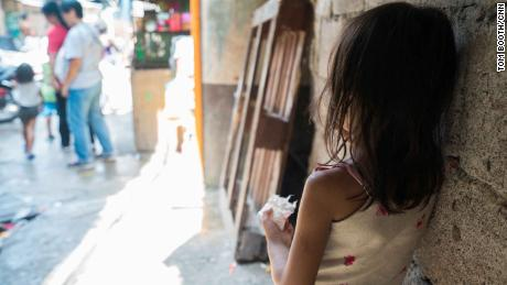 A young girl looks on a bustling street in Manila's Tondo neighborhood.