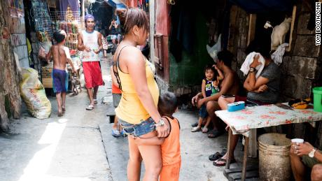 A woman stands in an alley in Tondo, a child clutching her leg.