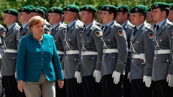 German Chancellor Angela Merkel greets the soldiers of the military honour guard ahead of the welcoming ceremony for Estonia