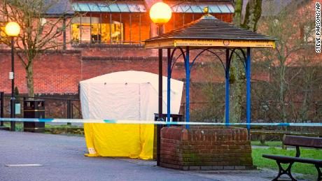Investigators leave the park bench in Salibury covered with a forensic tent Tuesday.