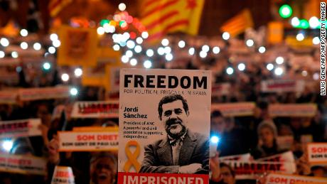 "People hold a banners reading ""Free political prisoners"" depcting an image of Catalan separatist leaders Jordi Sanchez in Barcelona on January 16 , 2018 during a demonstration calling for the release of Catalan separatist leaders Jordi Sanchez and Jordi Cuixart, jailed three months ago.  / AFP PHOTO / LLUIS GENE        (Photo credit should read LLUIS GENE/AFP/Getty Images)"