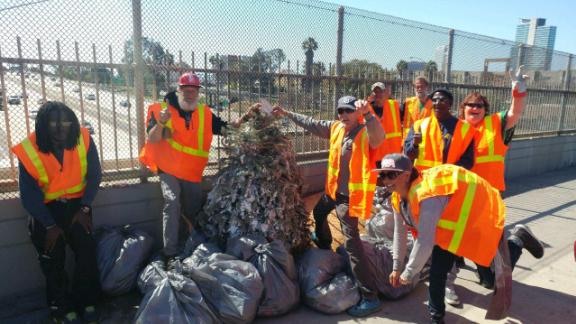 Homeless workers pose with  trash they cleaned up from the streets of San Diego.