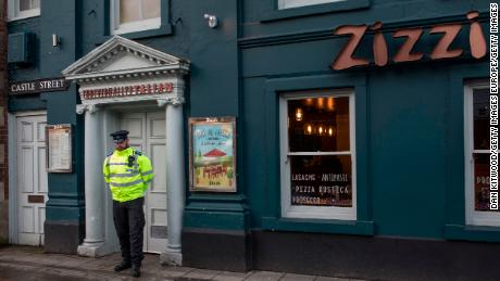 An officer stands outside the nearby Zizzi restaurant, which was closed Tuesday.