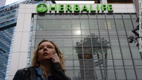 A woman is seen speaking on her cellphone beneath a Herbalife sign atop an office building in downtown Los Angeles on January 24, 2014.  A US Senator is urging federal regulators to investigate the business practices of Herbalife Ltd., the Los Angeles maker of nutrition and personal care products. Massachusetts Democrat Edward J. Markey asked the Securities and Exchange Commission and Federal Trade Commission to investigate Herbalife,  with concern coming some 13 months after hedge fund manager Bill Ackman accused Herbalife of operating a pyramid scheme. AFP PHOTO/Frederic J. BROWN        (Photo credit should read FREDERIC J. BROWN/AFP/Getty Images)