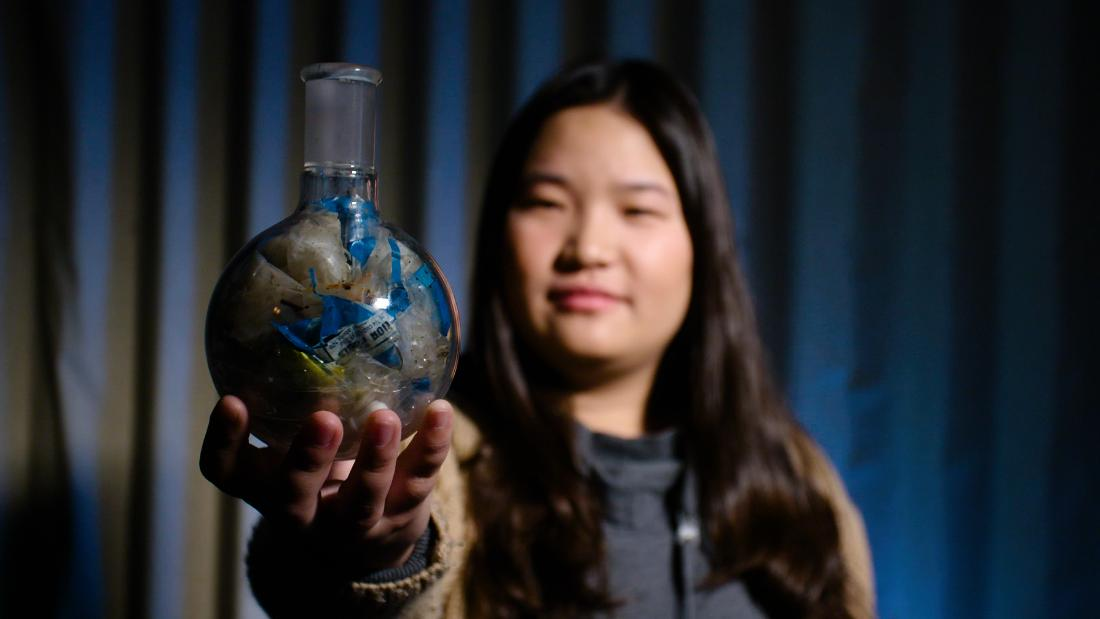 Miranda Wang holds up a spherical flask containing waste plastic film. Normally considered unrecyclable, her start-up BioCellection can break down the plastic for reuse with a chemical catalyst.