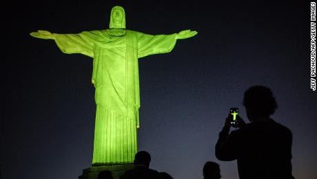 TOPSHOT - Visitors stand under the Christ the Redeemer statue on Corcovado mountain ahead of the Rio 2016 Olympic Games in Rio de Janeiro on August 4, 2016. / AFP / JEFF PACHOUD        (Photo credit should read JEFF PACHOUD/AFP/Getty Images)