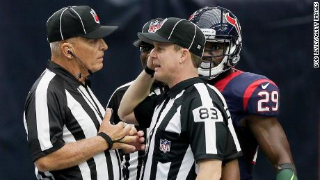 Shawn Hochuli (No. 83) and field judge Tom Hill discuss a flag thrown on a play in 2016.
