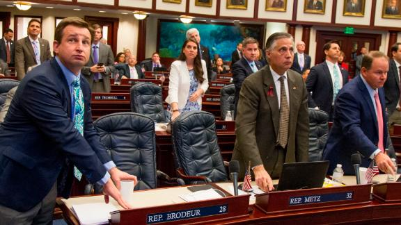 Florida Rep. Jason Brodeur, left, (R- Sanford), watches the vote board as he votes on the school safety bill which passed the House 67-50 at the Florida Capital in Tallahassee, Fla., Wednesday, March 7, 2018. (AP Photo/Mark Wallheiser)