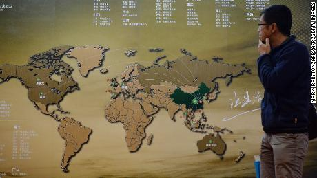 A Chinese investor walks past an investment map showing suitable property markets for wealthy Chinese to invest in at the International Property Expo in Beijing on April 11, 2014.  Wealthy Chinese will pour AUD$44 billion (US$39.4 billion) into Australian real estate over the next seven years, potentially pushing prices in one of the world's most expensive housing markets even higher. Chinese property investors have been on a international spending spree since the global financial crisis hit most of the world's economies.      AFP PHOTO/Mark RALSTON        (Photo credit should read MARK RALSTON/AFP/Getty Images)