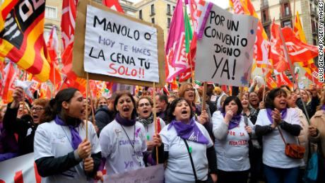 "Demonstrators hold a placard reading ""Manolo today you'll do your dinner on your own"" during the one-day strike in Barcelona."