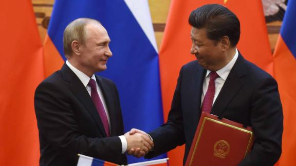 Russian President Vladimir Putin (L) shakes hands with Chinese President Xi Jinping during a signing ceremony in Beijing
