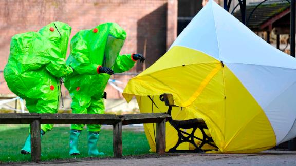 """TOPSHOT - Members of the emergency services in green biohazard suits afix the tent over the bench where a man and a woman were found on March 4 in critical condition at The Maltings shopping centre in Salisbury, southern England, on March 8, 2018 after the tent became detached.  British detectives on March 8 scrambled to find the source of the nerve agent used in the """"brazen and reckless"""" attempted murder of a Russian former double-agent and his daughter. Sergei Skripal, 66, who moved to Britain in a 2010 spy swap, is unconscious in a critical but stable condition in hospital along with his daughter Yulia after they collapsed on a bench outside a shopping centre on Sunday.  / AFP PHOTO / Ben STANSALL        (Photo credit should read BEN STANSALL/AFP/Getty Images)"""