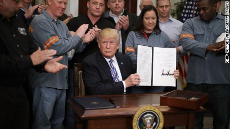 WASHINGTON, DC - MARCH 08:  Surrounded by applauding steel and aluminum workers, U.S. President Donald Trump holds up the 'Section 232 Proclamations' on steel imports that he signed in Roosevelt Room the the White House March 8, 2018 in Washington, DC. Trump announced last week that he will put a 25-percent tarriff on imported steel and a 10-percent tarriff on imported alumninum.  (Photo by Chip Somodevilla/Getty Images)