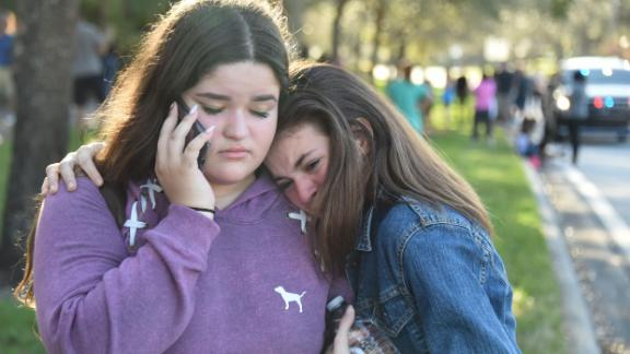 """TOPSHOT - Students react following a shooting at Marjory Stoneman Douglas High School in Parkland, Florida, a city about 50 miles (80 kilometers) north of Miami on February 14, 2018.A gunman opened fire at the Florida high school, an incident that officials said caused """"numerous fatalities"""" and left terrified students huddled in their classrooms, texting friends and family for help.The Broward County Sheriff"""
