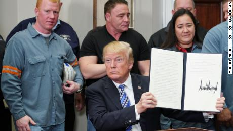 US President Donald Trump holds up the Section 232 proclamations on aluminum imports after signing it in the Roosevelt Room of the White House on March  8, 2018 in Washington, DC. / AFP PHOTO / MANDEL NGAN        (Photo credit should read MANDEL NGAN/AFP/Getty Images)