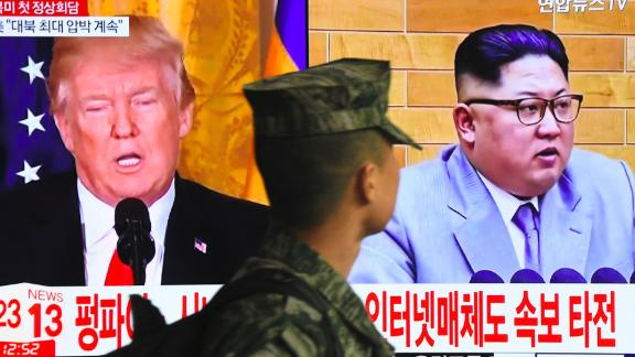 TOPSHOT - A South Korean soldier walks past a television screen showing pictures of US President Donald Trump (L) and North Korean leader Kim Jong Un at a railway station in Seoul on March 9, 2018.