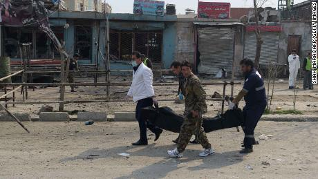 Afghan investigators carry away the body of the alleged assailant on Friday.