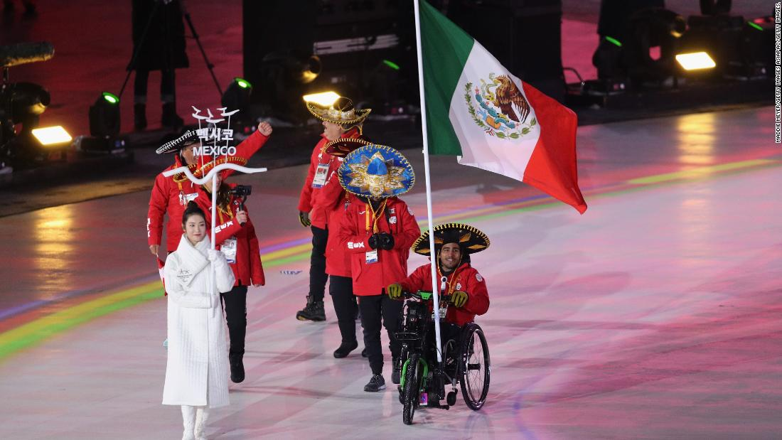 Mexico's sole competitor Arly Aristides Velasquez Penaloza carries his national flag into the arena.