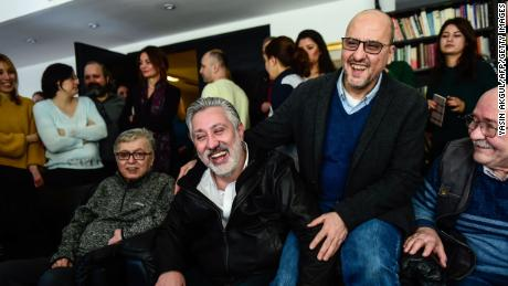 Colleagues welcome the release of Sabuncu, second left, and Sık, second right, on Saturday in Istanbul.