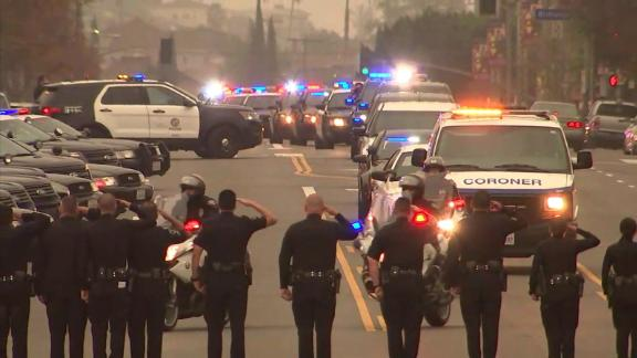 Law enforcement members honor the fallen officer as the coroner's van pulls away.