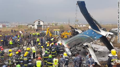"Nepali rescue workers gather around the debris of an airplane that crashed near the international airport in Kathmandu on March 12, 2018. At least 40 people were killed and 23 injured when a Bangladeshi passenger plane crashed near Kathmandu airport March 12, an official said. ""Thirty-one people died at the spot and nine died at two hospitals in Kathmandu,"" police spokesman Manoj Neupane told AFP, adding another 23 were injured. There were 67 passengers and four crew on board the US-Bangla Airlines plane from Dhaka.   / AFP PHOTO / Prakash MATHEMA        (Photo credit should read PRAKASH MATHEMA/AFP/Getty Images)"