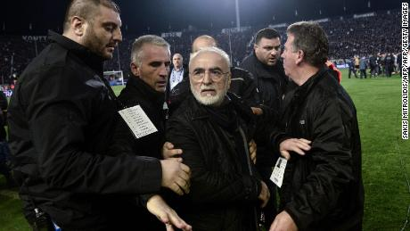 PAOK President Ivan Savvides escorted out after carrying a pistol onto the pitch