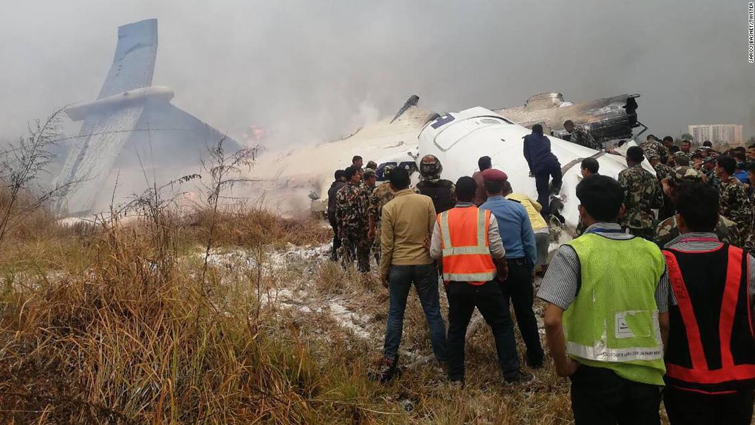 Rescuers survey the plane's smoking debris.