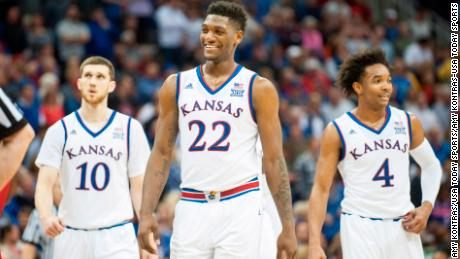Kansas Jayhawks guard Sviatoslav Mykhailiuk (10) and forward Silvio De Sousa (22) and guard Devonte' Graham (4) walk back on to the court after a time out against the West Virginia Mountaineers during the Big 12 Tournament final.