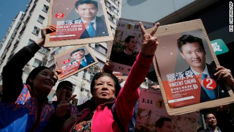 Supporters of Hong Kong pro-Beijing by-election candidate Vincent Cheng Wing-shun wave posters during an election campaign in Hong Kong, Sunday, March 11.