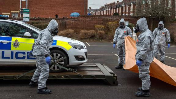 Military personnel wearing protective suits remove a police car and other vehicles from a public car park on March 11, 2018, in Salisbury, England.