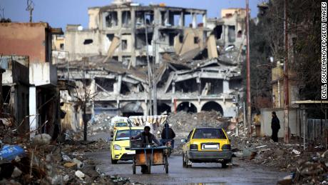 Syrians move along a destroyed street in Raqqa on February 18.