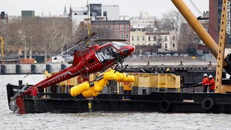 epa06598820 A crane lifts the sightseeing helicopter that crashed on Sunday night from the East River in New York, New York, USA, 12 March 2018. Five people died in the accident, though the pilot survived, and investigators from the National Transportation Safety Board are on the scene.  EPA/JUSTIN LANE