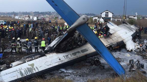 Nepali rescue workers gather around the debris of Flight BS 211.