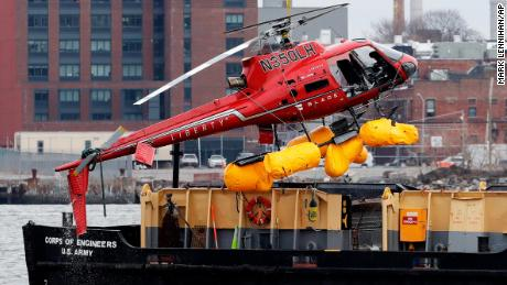 A helicopter is hoisted by crane from the East River onto a barge, Monday, March 12, 2018, in New York.