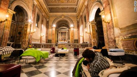 Inspired by Pope Francis' devotion to the poor, the Vatican-owned Santa Maria church offers beds to homeless migrants under priceless Renaissance frescoes.