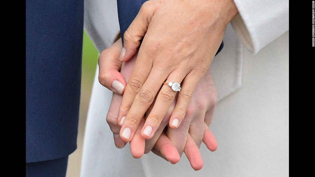 Meghan flashed her engagement ring to reporters during the November 2017 photo call. The ring, designed by Harry, has a gold band and features a large diamond from Botswana and two smaller outer diamonds from the personal collection of Harry's late mother.