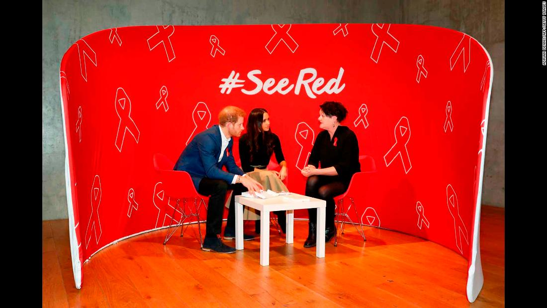 The couple talks with Dr. Laura Waters as they take part in a charity fair for World AIDS Day in December 2017.