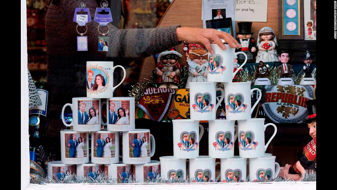 A shop worker in Windsor, England, adjusts memorabilia celebrating the engagement of Harry and Meghan.