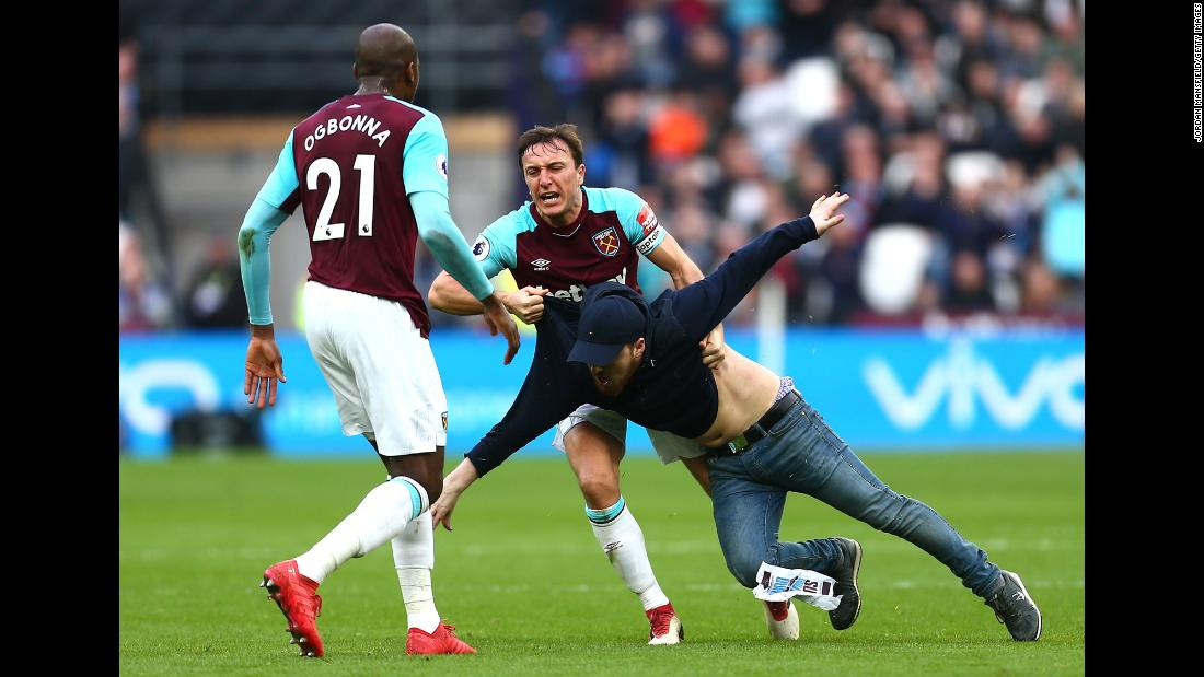 "West Ham captain Mark Noble clashes with one of several disgruntled supporters <a href=""http://bleacherreport.com/articles/2763661-west-ham-fans-invade-pitch-confront-players-during-loss-vs-burnley"" target=""_blank"">who ran onto the field</a> during the London club's 3-0 loss to Burnley on Saturday, March 10."