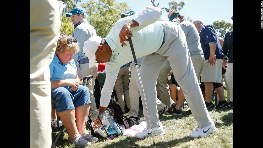 Tiger Woods removes his ball from a spectator's bag after a wayward shot at the Valspar Championship on Friday, March 9.
