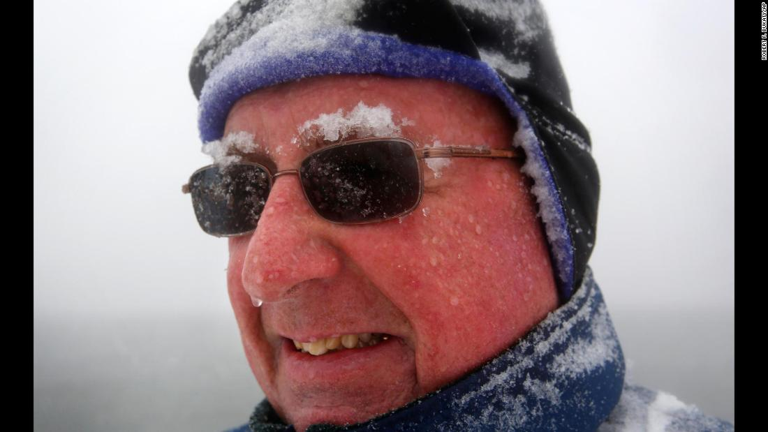 "Snow accumulates on Paul Knight's eyebrows as he walks in Portland, Maine, on March 13. ""We're not out of winter yet, that's for sure,"" he said."