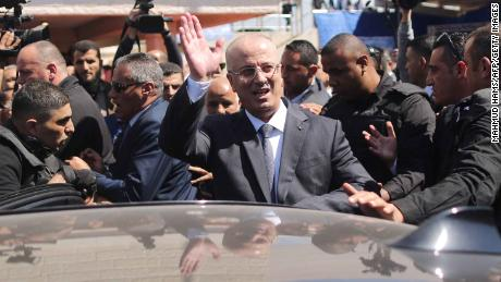 Palestinian Prime Minister Rami Hamdallah waves to the crowd upon his arrival in Gaza City on March 13, 2018. Hamdallah cut short a rare visit to Gaza on Tuesday after an explosion targeted his convoy, a source in the delegation said. The premier, who was not hurt, left the Hamas-run territory through the Erez crossing shortly after opening a wastewater treatment facility, the source said.   / AFP PHOTO / MAHMUD HAMS / The erroneous mention[s] appearing in the metadata of this photo by MAHMUD HAMS has been modified in AFP systems in the following manner: [Hamdallah waves to the crowd upon his arrival] instead of [Hamdallah (2nd-R) is greeted by Hamas' security chief Tawfiq Abu Naim (C) upon his arrival ]. Please immediately remove the erroneous mention[s] from all your online services and delete it (them) from your servers. If you have been authorized by AFP to distribute it (them) to third parties, please ensure that the same actions are carried out by them. Failure to promptly comply with these instructions will entail liability on your part for any continued or post notification usage. Therefore we thank you very much for all your attention and prompt action. We are sorry for the inconvenience this notification may cause and remain at your disposal for any further information you may require.        (Photo credit should read MAHMUD HAMS/AFP/Getty Images)