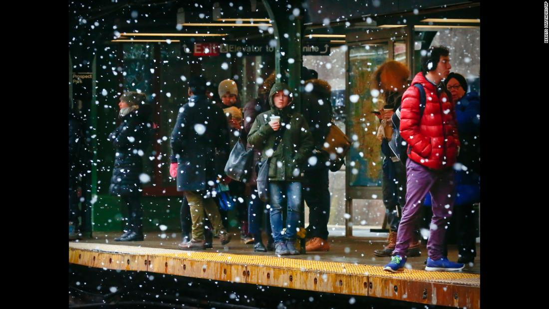 Commuters are sheltered from snowfall while they wait on a subway platform in New York City on March 13.