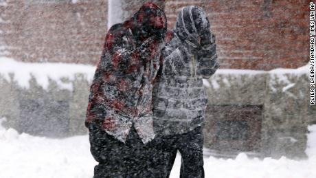 Two pedestrians make their way up the street as heavy snow falls in New Bedford, Mass., on Tuesday, March 13, 2018. A nor'easter that could deliver up to 2 feet of snow to some areas socked New England on Tuesday, bringing blizzard conditions to parts of coastal Massachusetts, covering highways with snow and knocking out power to tens of thousands.  (Peter Pereira /Standard Times via AP)