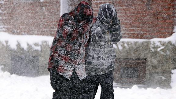 Heavy snow falls on two pedestrians in New Bedford, Massachusetts, on March 13.
