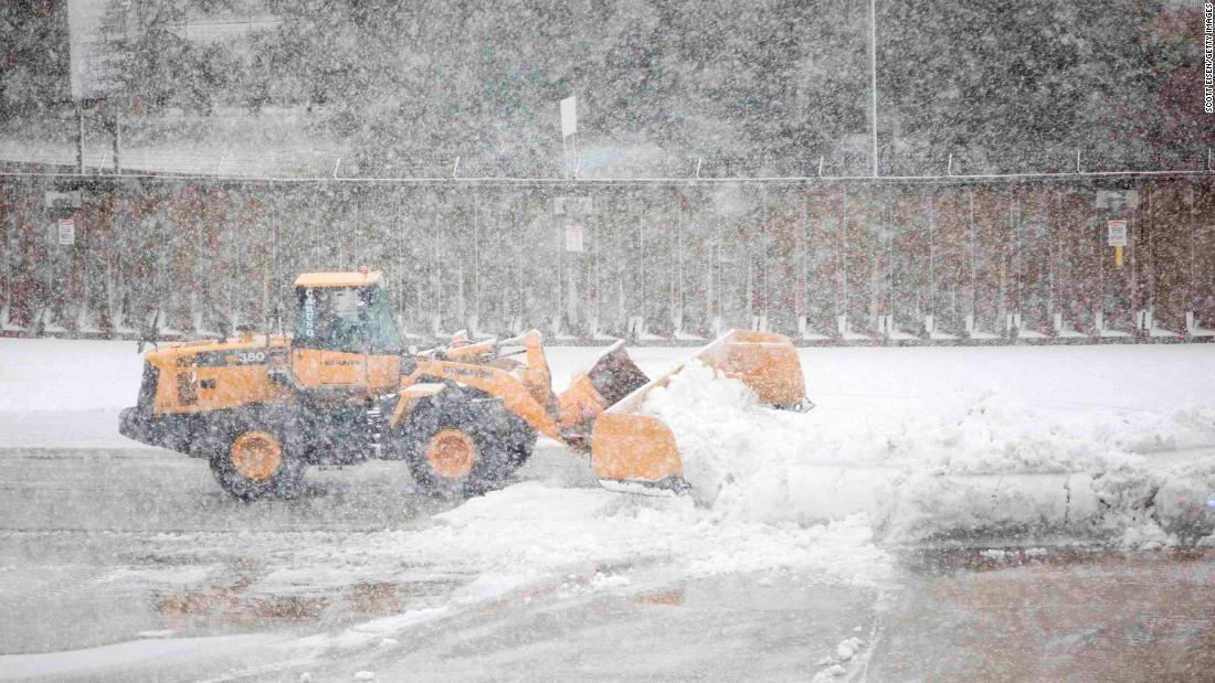 A snow plow clears a taxiway at Logan International Airport in Boston.