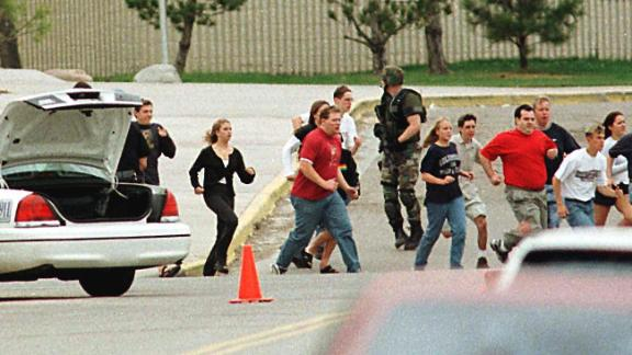Students from Columbine High School run under cover from police on April 20, 1999, in Littleton, Colorado.