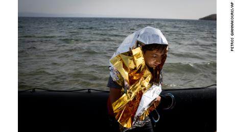 A young Syrian boy is wrapped with a thermal blanket as he arrives with others at the coast on a dinghy after crossing from Turkey, at the island of Lesbos, Greece.