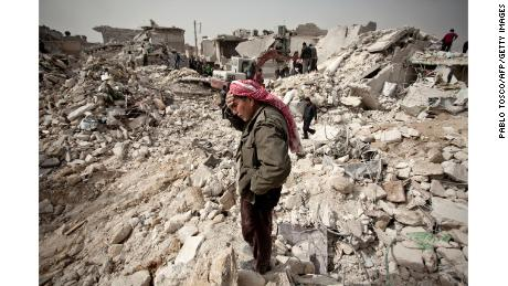 A Syrian man reacts while standing on the rubble of his house while others look for survivors and bodies in the Tariq al-Bab district of Aleppo.